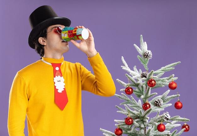 Jonge man in gele coltrui en bril met zwarte hoed en grappige stropdas drinken uit kleurrijke papieren beker staande naast een kerstboom over paarse muur