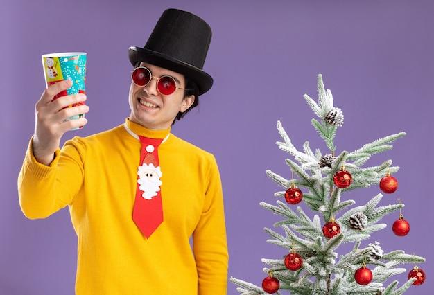 Jonge man in gele coltrui en bril met zwarte hoed en grappige stropdas met een kleurrijke papieren beker die ernaar kijkt met een glimlach op het gezicht naast een kerstboom over paarse muur