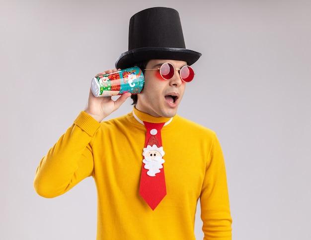 Jonge man in gele coltrui en bril met zwarte hoed en grappige stropdas met kleurrijke papieren beker over zijn oor proberen te luisteren staande op witte achtergrond