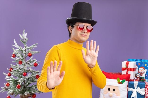 Jonge man in gele coltrui en bril met zwarte hoed kijken camera bezorgd hand in hand naast een kerstboom en presenteert over paarse achtergrond