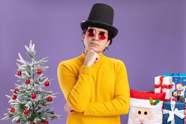 Jonge man in gele coltrui en bril met zwarte hoed opzij kijken met hand op kin denken staande naast een kerstboom en cadeautjes op paarse achtergrond