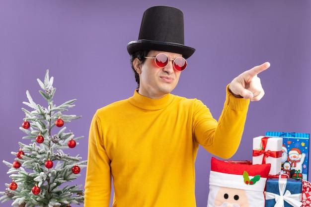 Jonge man in gele coltrui en bril met zwarte hoed opzij kijken ontevreden wijzend met wijsvinger naar iets staande naast een kerstboom en cadeautjes op paarse achtergrond