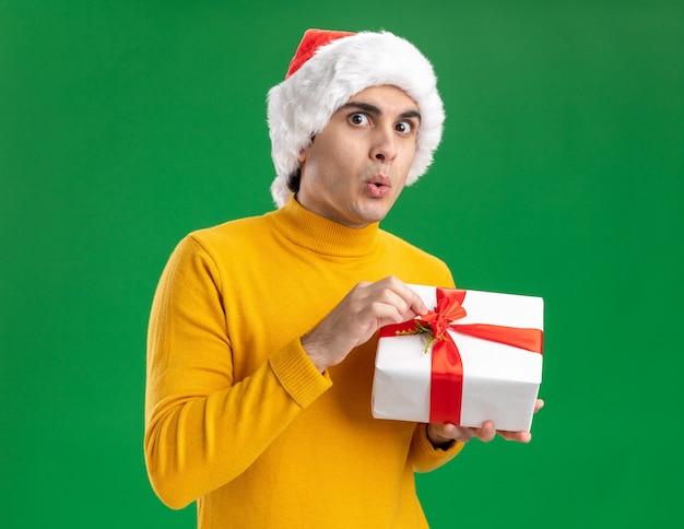 Jonge man in gele coltrui en kerstmuts met een cadeautje kijken camera verbaasd staande over groene achtergrond