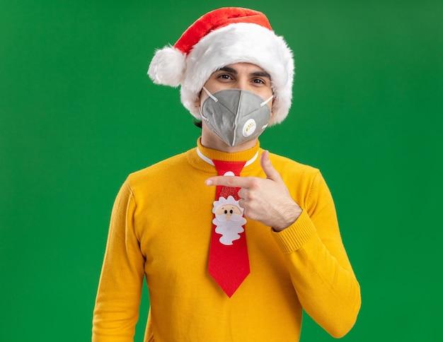 Jonge man in gele coltrui en kerstmuts met grappige stropdas dragen gezicht beschermend masker camera kijken met blij gezicht wijzend met wijsvinger naar de zijkant staande over groene achtergrond