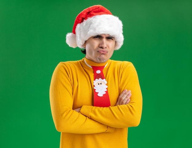 Jonge man in gele coltrui en kerstmuts met grappige stropdas kijken camera ontevreden maken wrange mond met teleurgestelde uitdrukking staande over groene achtergrond