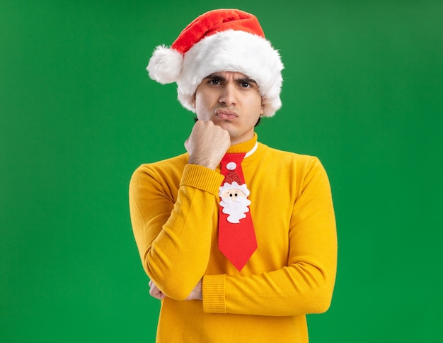 Jonge man in gele coltrui en kerstmuts met grappige stropdas kijken camera ontevreden met hand op zijn kin staande over groene achtergrond