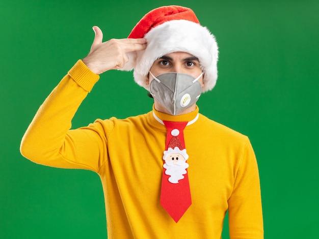 Jonge man in gele coltrui en kerstmuts met grappige stropdas met een beschermend gezichtsmasker die een pistoolgebaar maakt over de tempel die over een groene achtergrond staat