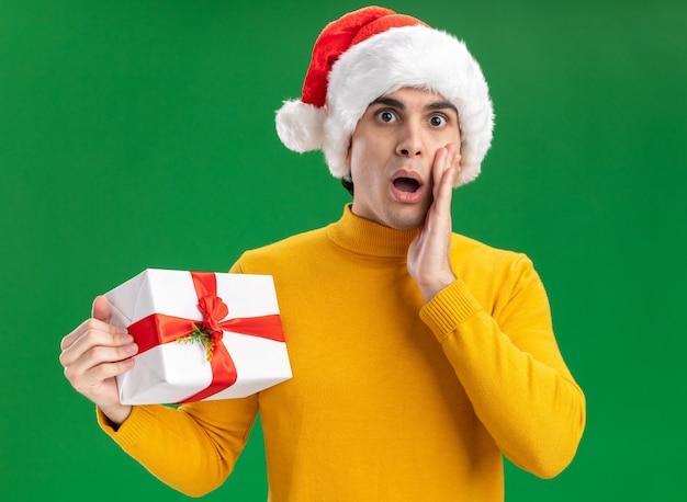 Jonge man in gele coltrui en kerstmuts met grappige stropdas met een geschenk verrast staande over groene muur