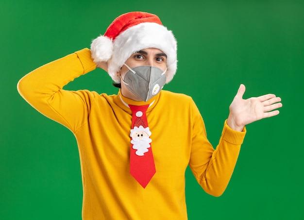Jonge man in gele coltrui en kerstmuts met grappige stropdas met gezichtsbeschermend masker kijkend naar camera verrast met opgeheven arm over groene achtergrond