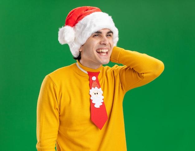 Jonge man in gele coltrui en kerstmuts met grappige stropdas opzij kijken met blij gezicht glimlachend vrolijk staande over groene achtergrond