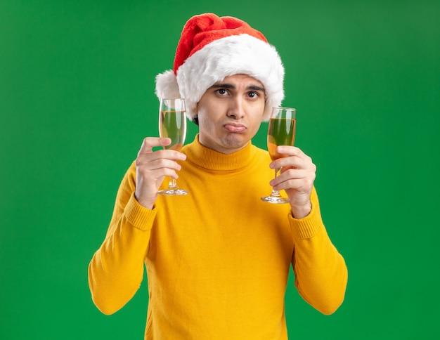 Jonge man in gele coltrui en kerstmuts met twee glazen champagne kijken camera met droevige uitdrukking staande over groene achtergrond