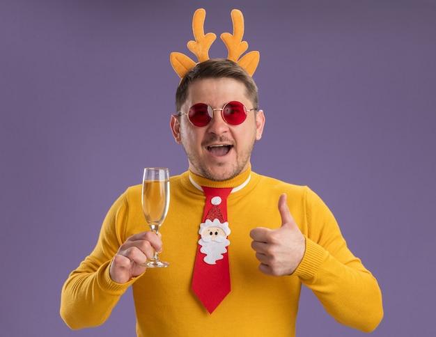 Jonge man in gele coltrui en rode bril dragen grappige rode stropdas en rand met herten hoorns houden glas champagne blij en vrolijk glimlachend duimen opdagen staande