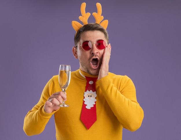 Jonge man in gele coltrui en rode bril dragen grappige rode stropdas en rand met herten hoorns houden glas champagne kijken camera verbaasd en verrassend staande over paarse achtergrond