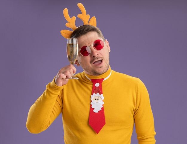 Jonge man in gele coltrui en rode bril dragen grappige rode stropdas en rand met herten hoorns kijken camera blij en positief houden glas champagne staande over paarse achtergrond