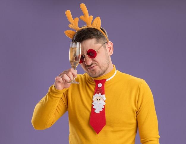Jonge man in gele coltrui en rode bril dragen grappige rode stropdas en rand met herten hoorns met glas champagne op zoek verward en zeer teleurgesteld staande over paarse achtergrond