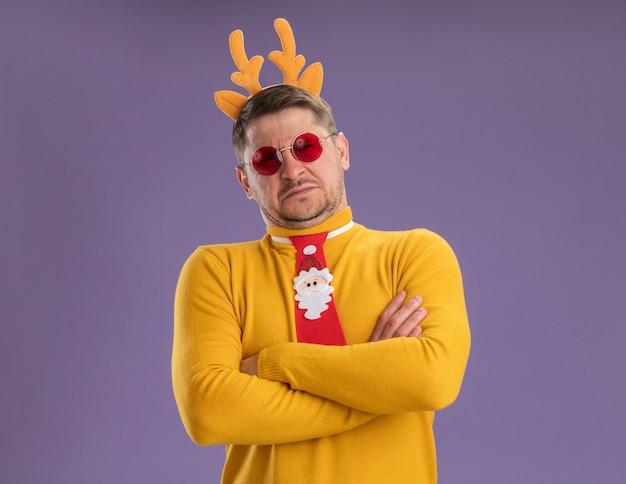Jonge man in gele coltrui en rode bril dragen grappige rode stropdas en rand met herten hoorns op hoofd camera kijken ontevreden met gekruiste armen staande over paarse achtergrond