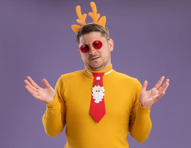 Jonge man in gele coltrui en rode bril dragen grappige rode stropdas en rand met herten hoorns op hoofd camera kijken verward schouderophalend schouders staande over paarse achtergrond kijken
