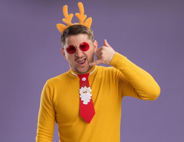 Jonge man in gele coltrui en rode bril dragen grappige rode stropdas en rand met herten hoorns op hoofd kijken camera blij en vrolijk bel me gebaar staande over paarse achtergrond kijken