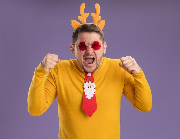 Jonge man in gele coltrui en rode bril dragen grappige rode stropdas en rand met herten hoorns op hoofd schreeuwen met agressieve expressie balde vuisten staande over paarse achtergrond