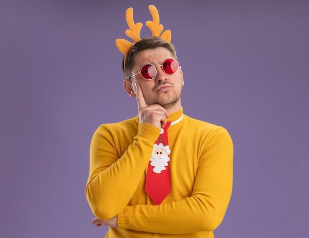 Jonge man in gele coltrui en rode bril dragen grappige rode stropdas en rand met herten hoorns opzoeken met peinzende uitdrukking denken staande over paarse achtergrond
