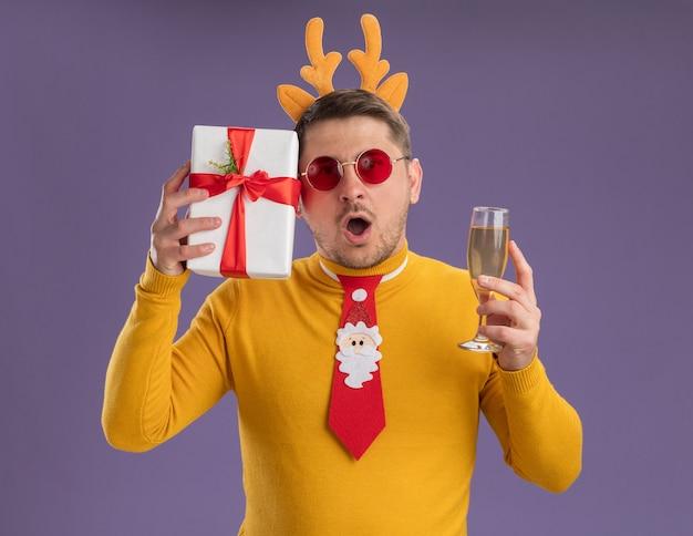 Jonge man in gele coltrui en rode bril met grappige rode stropdas en rand met herten hoorns met glas champagne en heden kijkt verbaasd en verbaasd staande over paarse achtergrond