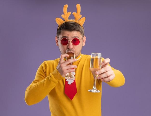 Jonge man in gele coltrui en rode bril met grappige rode stropdas en rand met herten hoorns met twee glazen champagne blij en positief staande over paarse achtergrond