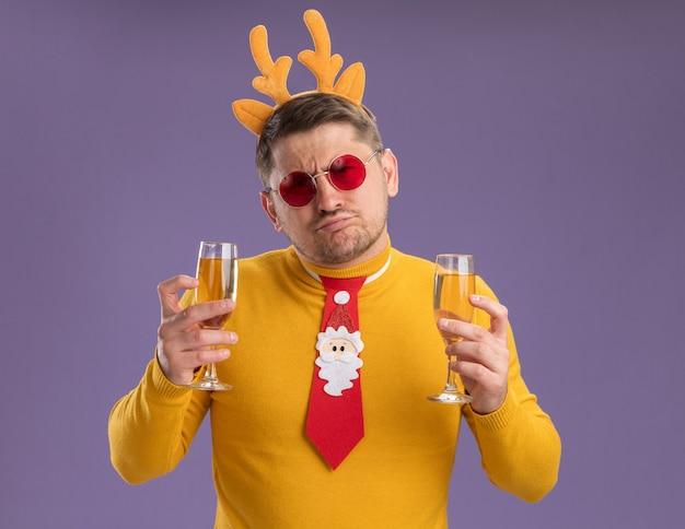 Jonge man in gele coltrui en rode bril met grappige rode stropdas en rand met herten hoorns met twee glazen champagne op zoek verward en ontevreden staande over paarse achtergrond