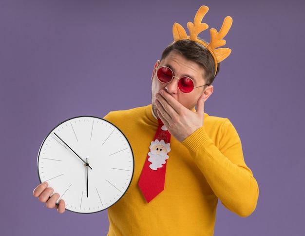 Jonge man in gele coltrui en rode bril met grappige rode stropdas en rand met herten hoorns op hoofd kijken verbaasd en verbaasd staande over paarse achtergrond