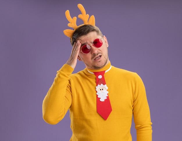 Jonge man in gele coltrui en rode bril met grappige rode stropdas en rand met herten hoorns op hoofd op zoek verward en erg angstig staande over paarse achtergrond