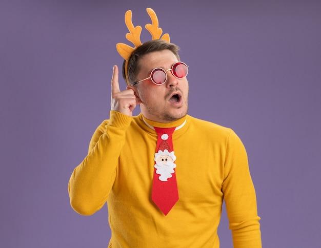 Jonge man in gele coltrui en rode bril met grappige rode stropdas en rand met herten hoorns op hoofd opzij kijken verbaasd tonen wijsvinger met nieuw geweldig idee staande over paarse achtergrond
