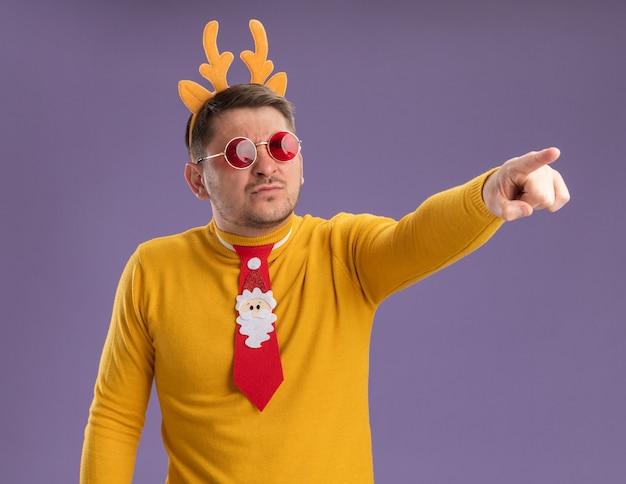 Jonge man in gele coltrui en rode bril met grappige rode stropdas en rand met herten hoorns op hoofd opzij kijken verward wijzend met wijsvinger naar iets staande over paarse achtergrond