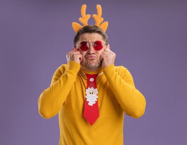 Jonge man in gele coltrui en rode bril met grappige rode stropdas en rand met herten hoorns opzoeken verward en teleurgesteld staande over paarse achtergrond