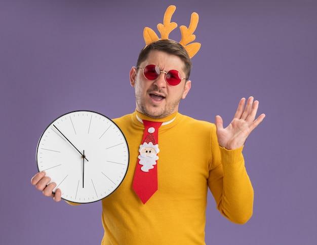Jonge man in gele coltrui en rode bril met grappige rode stropdas en rand met herten hoorns
