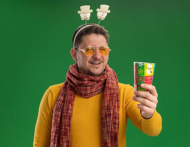 Jonge man in gele coltrui met warme sjaal en bril met grappige rand op het hoofd met kleurrijke beker kijkend met een glimlach op het gezicht staande over groene muur