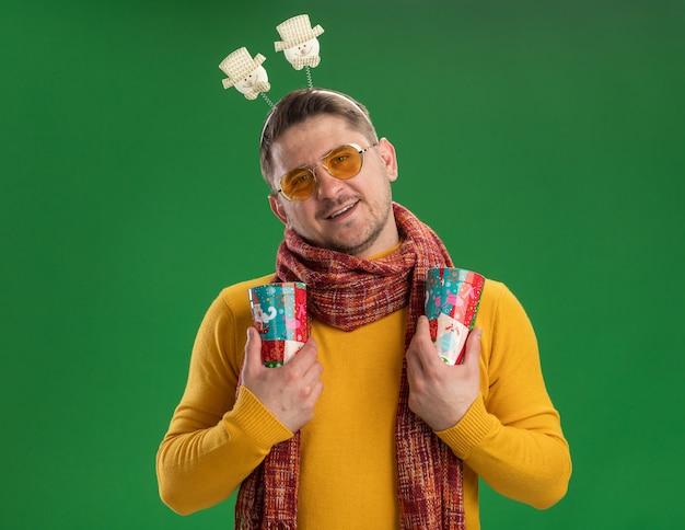 Jonge man in gele coltrui met warme sjaal en bril met grappige rand op hoofd met kleurrijke kopjes met glimlach op gezicht staande over groene muur