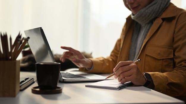 Jonge man in gele jas online werken met laptop thuis.