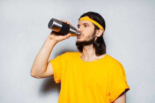 Jonge man in gele tshirt drinkwater uit stalen herbruikbare thermofles op grijze achtergrond.