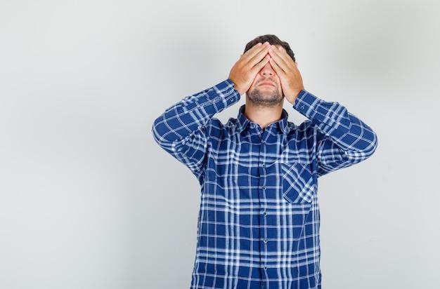 Jonge man in geruit overhemd dat ogen behandelt met handen en negatief kijkt