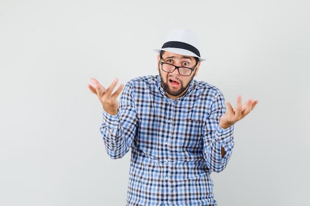 Jonge man in geruit overhemd, hoed die vraaggebaar maakt en verbaasd, vooraanzicht kijkt.