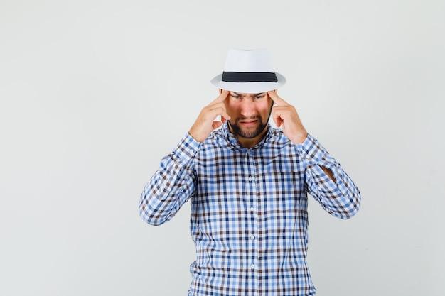 Jonge man in geruit overhemd, hoed lijdt aan sterke hoofdpijn en kijkt geïrriteerd, vooraanzicht.
