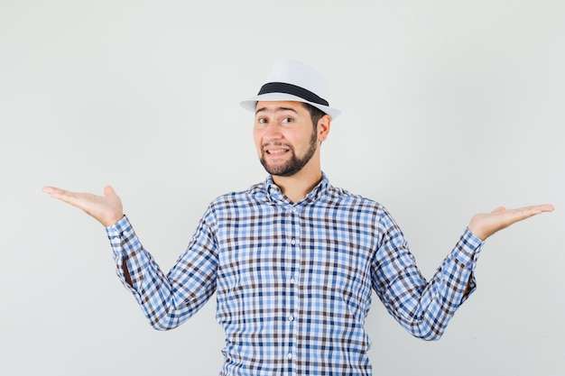 Jonge man in geruit overhemd, hoed schalen gebaar maken en op zoek vrolijk, vooraanzicht.