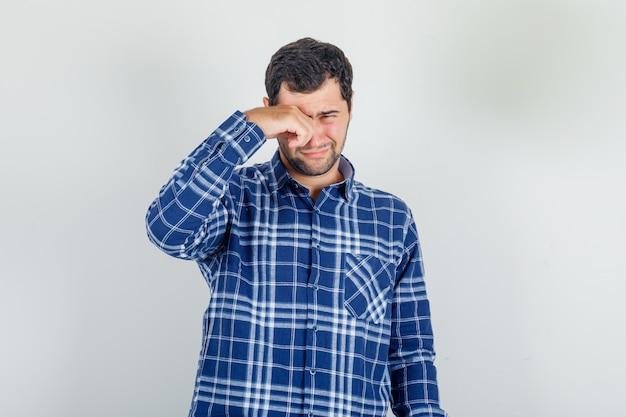 Jonge man in geruit overhemd huilen als een kind en verdrietig kijken