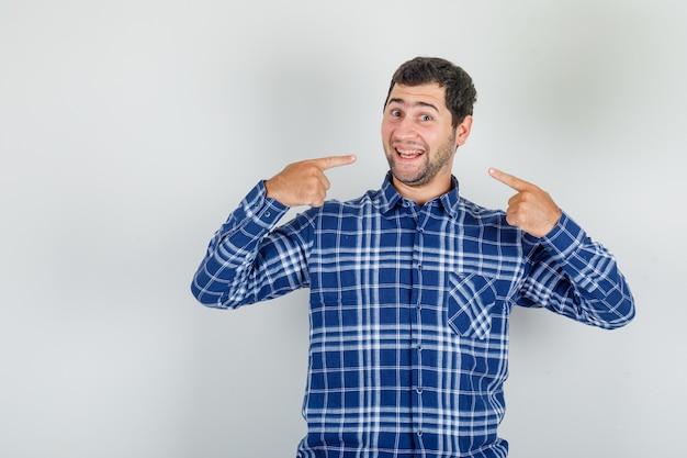 Jonge man in geruit overhemd toont zichzelf met vingers en kijkt vrolijk