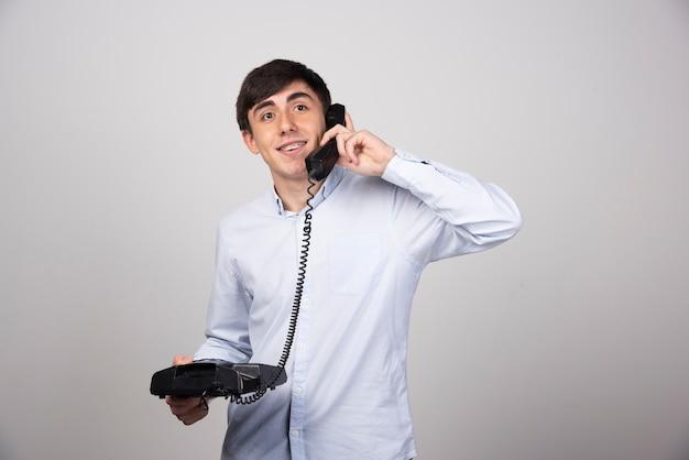 Jonge man in gesprek met iemand via vaste telefoon op grijze muur.