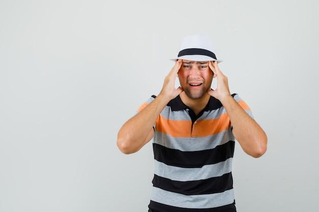 Jonge man in gestreept t-shirt, hoed die aan hoofdpijn lijdt en pijnlijke ruimte voor tekst zoekt
