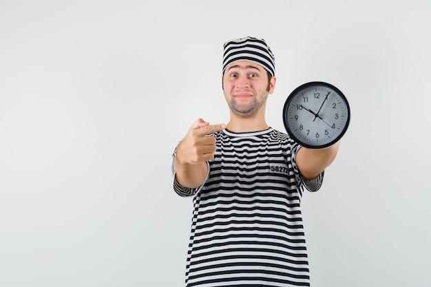 Jonge man in gestreept t-shirt, pet wijzend op de klok en kijkt blij, vooraanzicht.