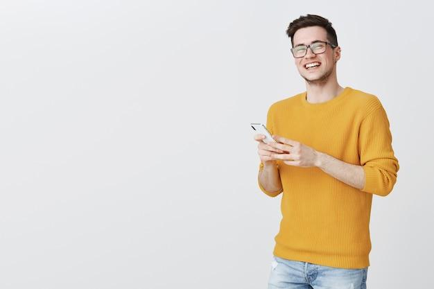Jonge man in glazen lachen als het gebruik van mobiele telefoon