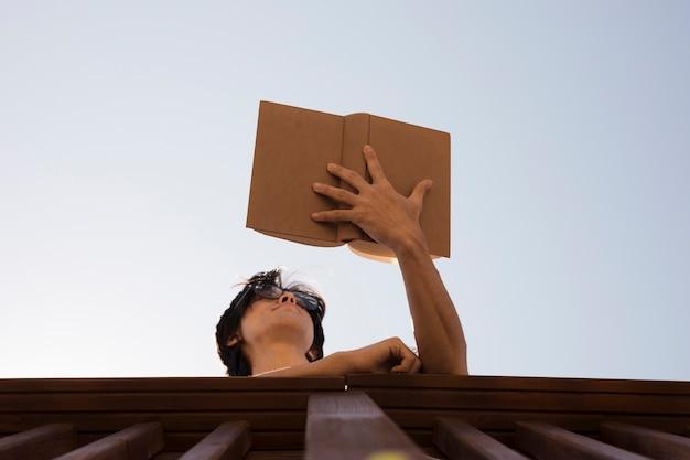 Jonge man in glazen lezen boek in de buurt van hek