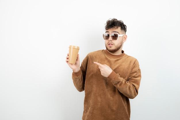 Jonge man in glazen met kopje koffie.