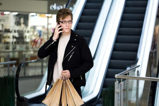 Jonge man in glazen met papieren zakken winkelen in het winkelcentrum en praten aan de telefoon